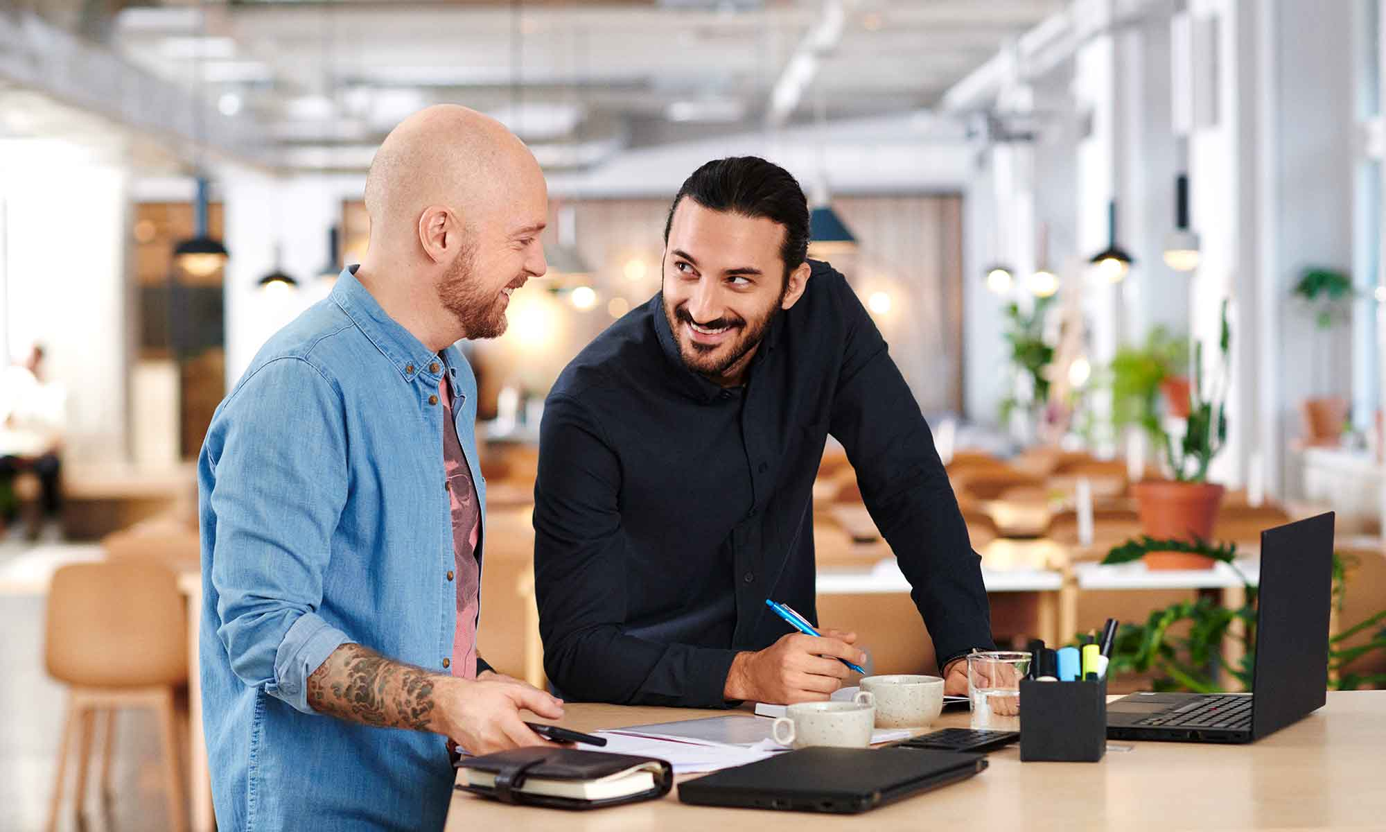 Two men at a workplace smiling at each other